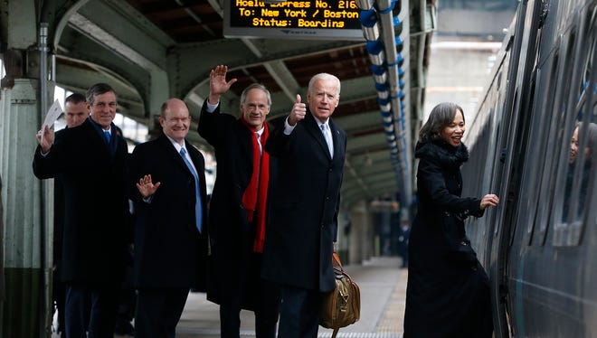 Delaware Gov. John Carney, left, Sens. Chris Coons and Tom Carper, now-President Joe Biden and Rep. Lisa Blunt Rochester board an Amtrak Acela train at Union Station bound for Wilmington, Del., after attending inauguration events on Jan. 20, 2017.