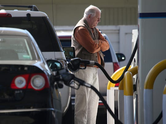 A customer pumps gasoline into his car at an Arco gas