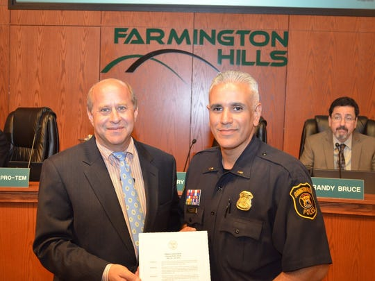 Farmington Hills Police Assistant Chief Dan Rodriguez (right, accepting a National Police Week proclamation from Councilman Richard Lerner) said the Hope Not Handcuffs program could get people help faster with medical attention.