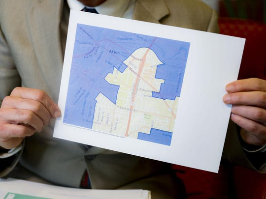 """David Niven, a professor of political science at the University of Cincinnati holds a map demonstrating a gerrymandered Ohio district, April 11, 2019, in Cincinnati. """"The point of this map was to build a seawall against the storm, and it has held,"""" Niven said."""