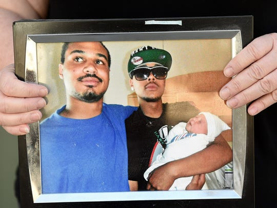 Deana Connelly holds a photograph of her two sons Ryan Connelly, 17, left, and Kevin Connelly, 24.Ryan was shot and killed on July 7th, 2012 while walking home from the store.
