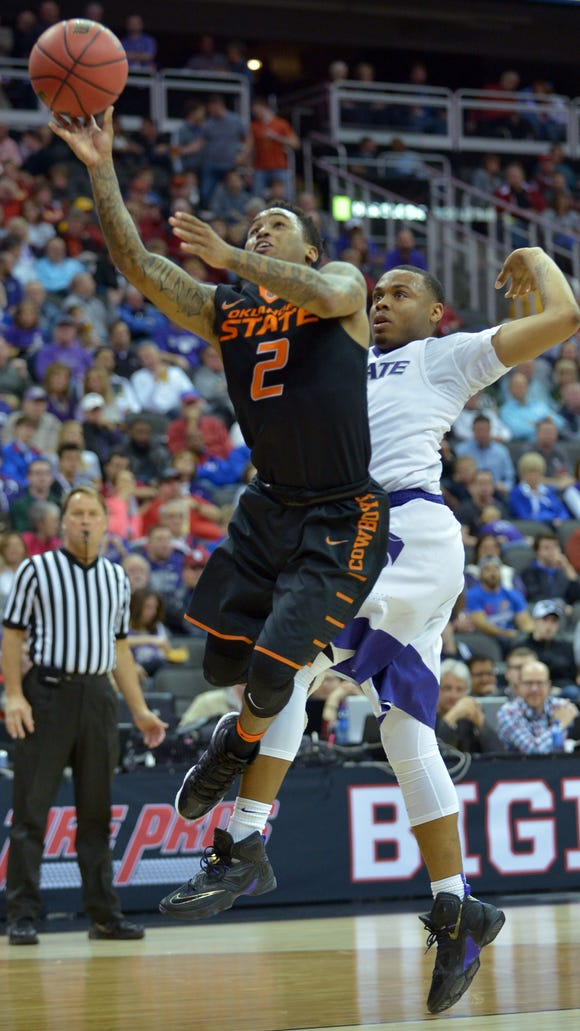 Oklahoma State Cowboys guard Tyree Griffin (2) shoots the ball in front of Kansas State guard Justin Edwards (14) in the first half during the Big 12 Conference tournament.
