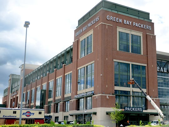 Workers are installing signs for the new Packers Pro Shop at Lambeau Field.