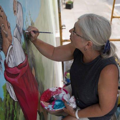 Mural artist Pam Kellough repaints a mural on the brick