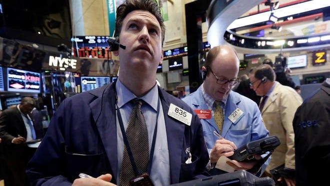 Glenn Kessler, left, works with fellow traders on the floor of the New York Stock Exchange.