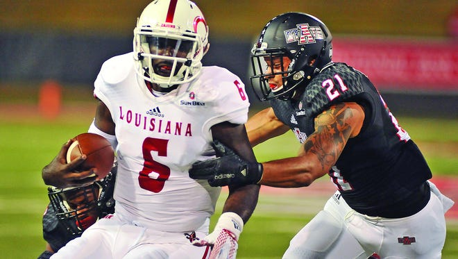 UL quarterback Jalen Nixon (6) is chased by Arkansas State defensive backs Money Hunter (27) and Cody Brown (21) during Tuesday's Sun Belt Conference game at Centennial Bank Stadium in Jonesboro, Ark.