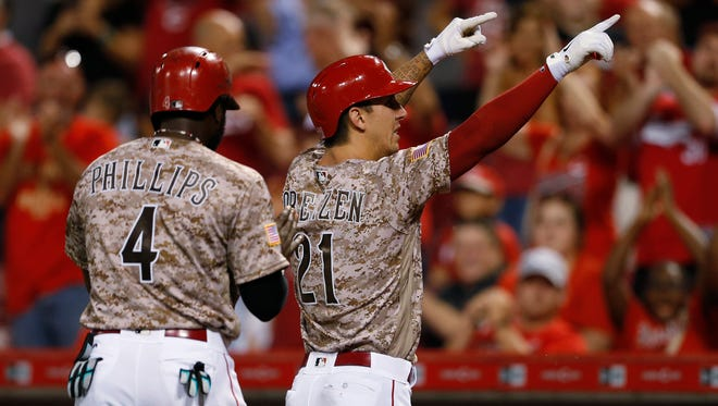 The Cincinnati Reds' Michael Lorenzen, right, points to the fans after hitting a three-run home run, his first career home run, off Los Angeles Dodgers relief pitcher Pedro Baez during the seventh inning of a baseball game, Friday, Aug. 19, 2016, in Cincinnati. At left is Brandon Phillips. The Reds won 9-2.