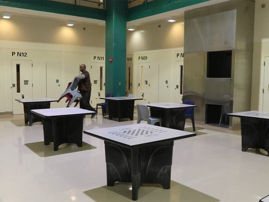 Kyle Butler, U.S. Army veteran, sets up the tables for breakfast in the veterans unit of the Monroe County Jail.