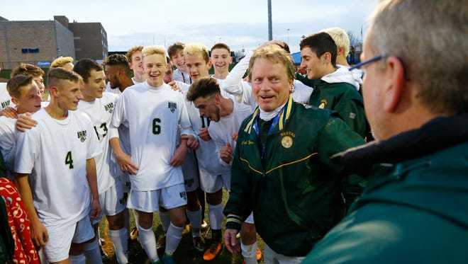 Vestal boys soccer coach, Dave Barr surrounded by his team after winning the New York State Championship in Middletown on Sunday, November 12, 2017.