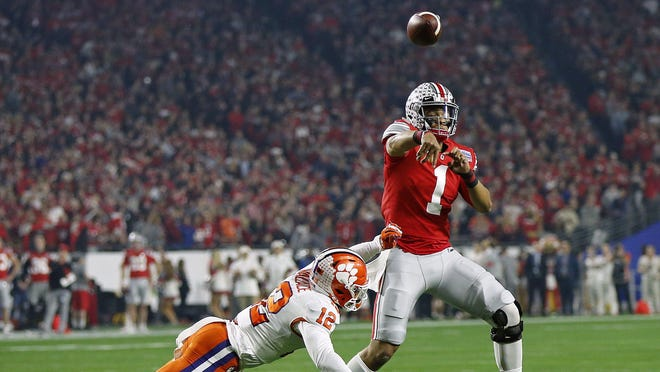 Ohio State quarterback Justin Fields, here throwing a pass while being pressured by Clemson safety K'Von Wallace in the College Football Playoff semifinal at the Fiesta Bowl in December, is among the players hoping to play college football in a safe manner this fall.