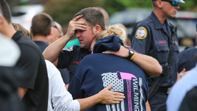 Wilmington firefighter Kevin Weems consoles Kate Maxwell during a vigil for Lt. Christopher Leach and Senior Firefighter Jerry Fickes at Salesianum School on Saturday. Leach and Fickes were killed in a fire in Canby Park.