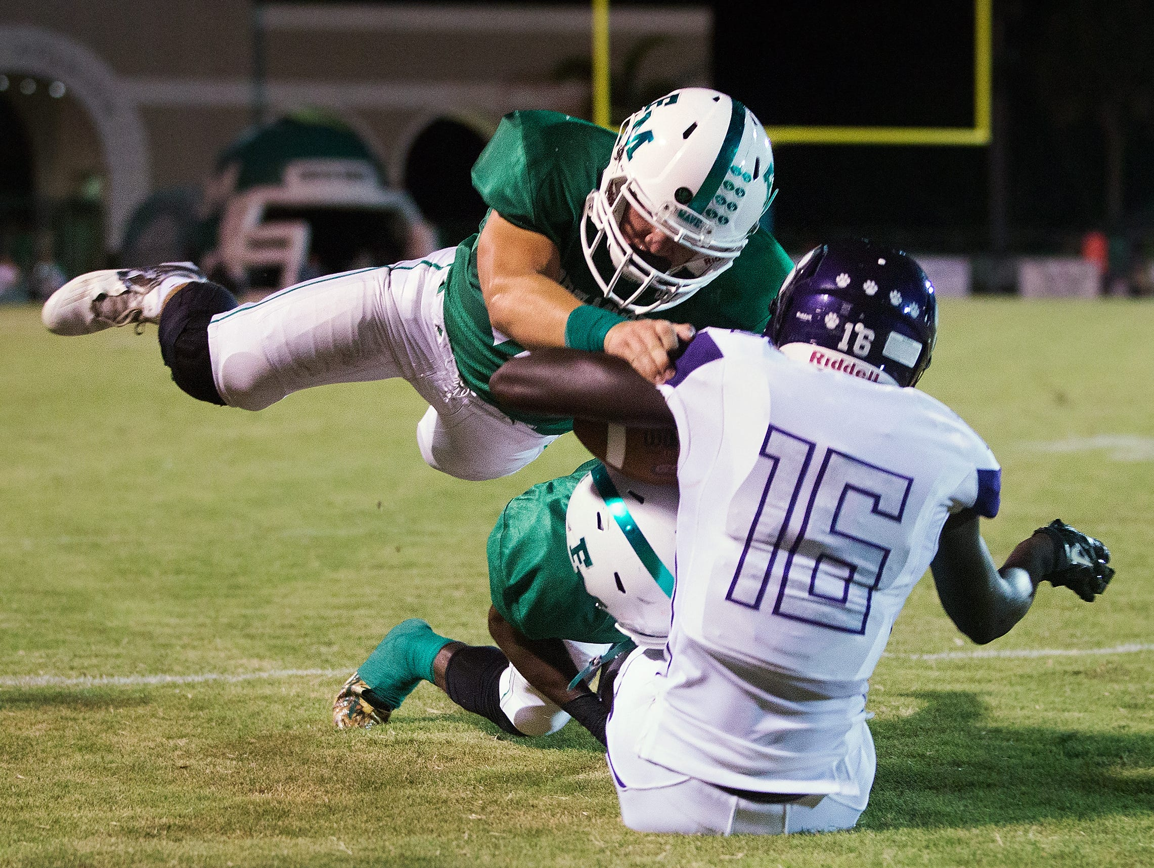 Fort Myers High School's Treyvon Curtis, bottom, and Matt McQuinn, top, tackle Cypress Lake's Tim Addison during second quarter play Friday at Fort Myers High School.