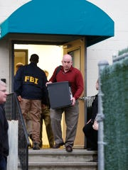 Federal agents remove boxes of collected evidence and computer hardware from the office of Hashomer Alarm Inc, at 29 Robert Pitt Drive in Spring Valley on Wednesday, March 16, 2016.