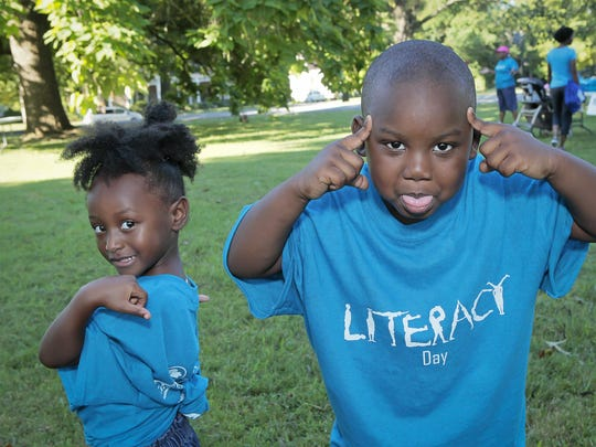 Three-year-old Dannia Gibbs and her 5-year-old brother, Little Ray, put on their game faces during registration for the Literacy Walk Saturday morning at Central Magnet High. Participants walked from Central Magnet down East Main Street to the City Plaza.