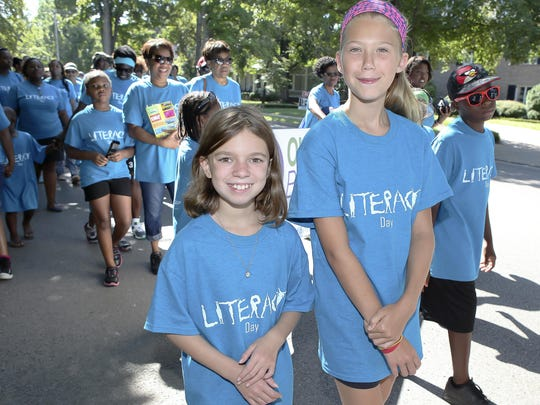 Hana King, left, and Haylie Smith, both Siegel Middle sixth-graders, march down East Main Street to the City Plaza during the Literacy Walk Saturday morning.