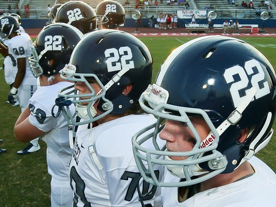 Members of the Siegel High School football treat wear helmets with the number 22 to honor Mason Loupe, a Siegel player who died on Wednesday.