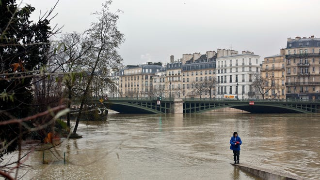 A woman walks along a low wall on the flooded banks of the river Seine in Paris, on Jan. 27, 2018.