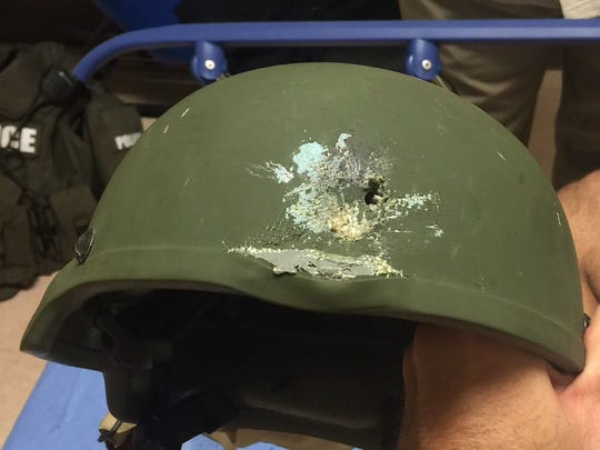 This handout photo provided by the Orlando Police Department on June 12, 2016, shows a bullet hole left in a kevlar helmet worn by an Orlando police officer that saved his life during the shootings at the Pulse nightclub in Orlando, Fla.