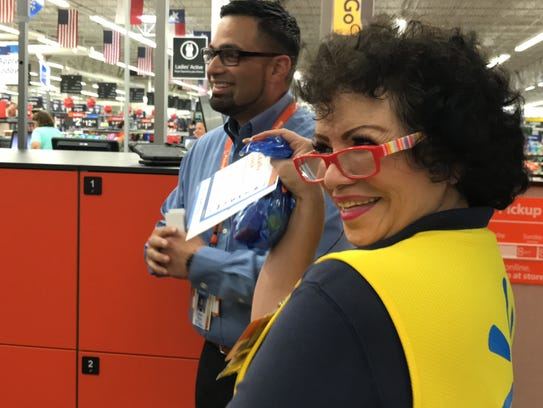 Sandra Martinez, a Walmart employee, shows off a sample goodie bag to employees after trying out the new automated pickup machine in the Calallen store Feb. 16, 2018. The pickup machine is the first one in Corpus Christi and one of four in the South Texas region.