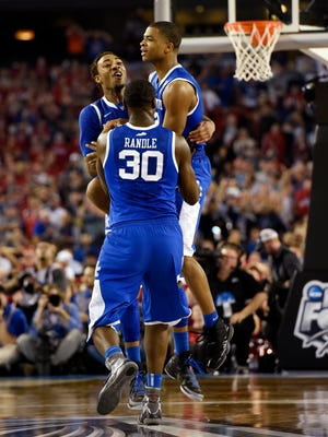Kentucky guard Aaron Harrison (2) celebrates with teammates Julius Randle (30) and James Young after making the winning three-pointer.