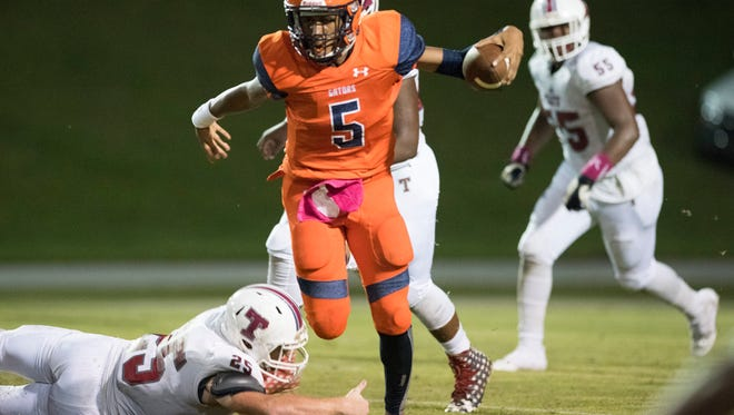 Escambia High quarterback, AV Smith, (5) tiptoes past Tate High linebacker Anthony Stafford, (N25) during a game on Friday night at Escambia High.