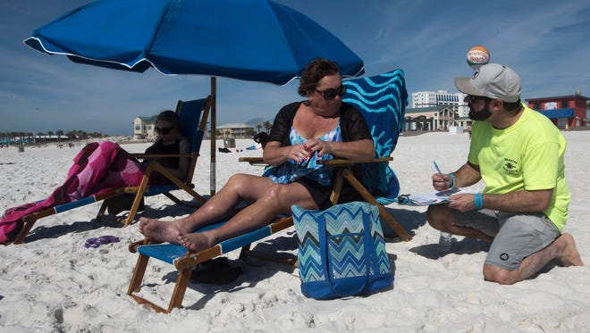 Patti Coote, center, rents her beach chair from Nick Ponzini, of Lazy Days Beach Rentals, on Monday, Feb. 19, 2018, at Casino Beach. Pensacola Beach leaders have changed an ordinance governing beach vendors to allow more chair and umbrella rentals on the busiest beach days.