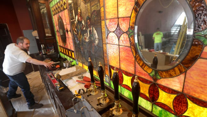 Jordin Franz, left, and Mike Jackman, reflected in mirror, work on the interior of McFleshman's Brewing Co. in Appleton.