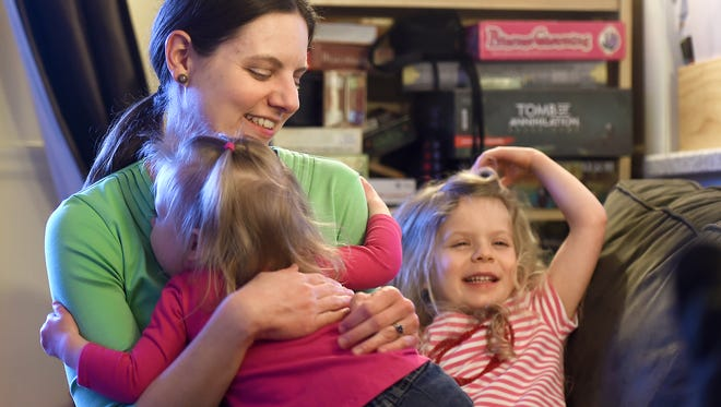 Hanni Wenzel Fuentes holds her daughter Brook while daughter Autumn looks on in the family's Chenango Bridge home.