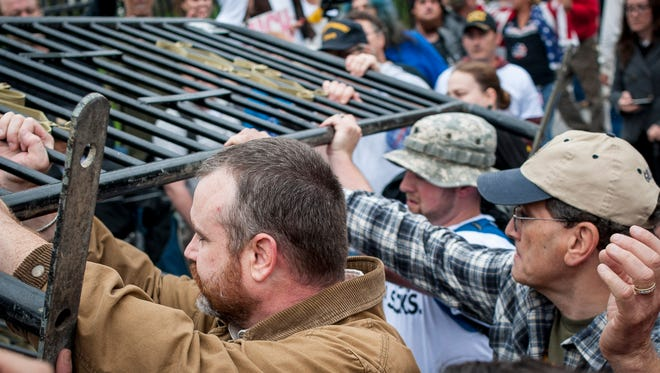 Protesters carry barriers taken from the  National World War II Memorial to the White House during a protest Oct. 13 in Washington.