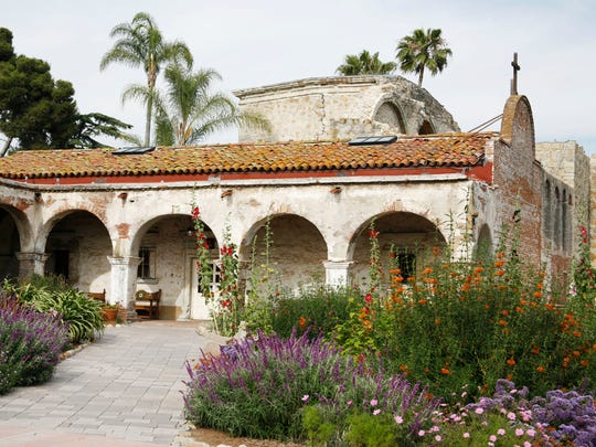 A view of the Capistrano mission, include an old stone building with arches and the surrounding gardens.