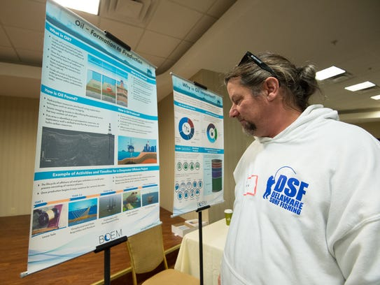 Rich King of Delaware Surf Fishing looks at an oil formation-to-production poster during a meeting held by the Bureau of Ocean Energy Management to discuss the newly proposed national outer continental shelf oil and gas leasing program for 2019-2024.