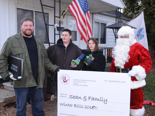 Sean Ralston and his kids, Bailey and Connor, are presented with a check to help cover their winter bills by Santa (Norman Yatooma) this past Saturday in Garden City.