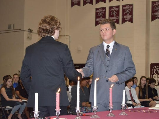 Caravel Academy's Robert Heath III is inducted into the music honor society Tri M by President Ryan Doyle.