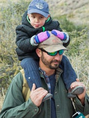 Max Tenorio and his 2-year-old son Max hike through