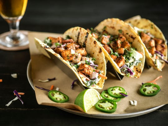 Blackened mahi tacos are served in grilled tortillas and garnished with tartar sauce and fresh cilantro at World of Beer.