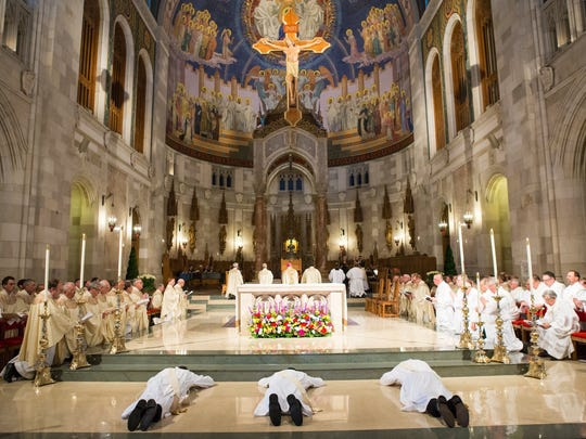 The Rev. Andrew Wellman, the Rev. Scott Perry and the Rev. Kyle Gase lay prostrate prior to ordination while the congregation chants the Litany of the Saints in Rosary Cathedral, Toledo.