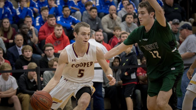 Covington Catholic's TJ Deere (5) dribble around Trinity's Stan Turnier (32) at the King of the Bluegrass Holiday Classic in Fairdale, Ky, Thursday, Dec. 22, 2017
