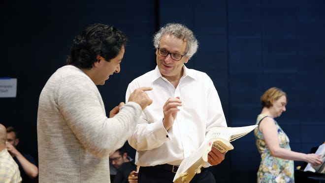 """Singer Rodion Pogossov, left, works with conductor Louis Langrée during a rehearsal for Cincinnati Opera's production of """"La Boheme."""""""