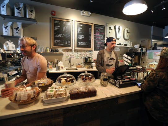 Barista Alejandro Diaz and owner Luis Corena work the