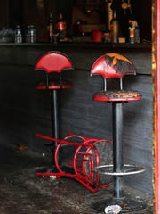Pictures of burned seats are taken in a French bar