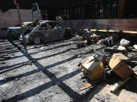 A pair of cars are burnt out amid damage from a fire that happened in a carport area Saturday night at Los Arboles Apartments in Indio. Photographed on Sunday morning, June 1, 2014.