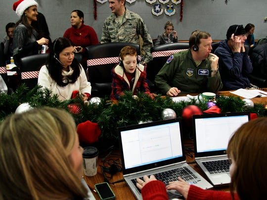 """U.S. Air Force Brig. Gen. Richard Scobie, right, his son Andrew, center, and wife, Janis, all take phone calls from children asking where Santa is and when he will deliver presents to their house, during the annual NORAD Tracks Santa Operation, at the North American Aerospace Defense Command, or NORAD, at Peterson Air Force Base, Colo. Santa is poised for another monster year on social media. NORAD Tracks Santa has already attracted a record 1.49 million Facebook """"likes"""" before the journey even begins. And for Christmas Eve 2014, there's a website version for smartphones."""