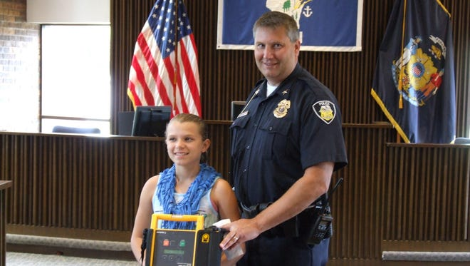 Maddie Kloehn, 11, poses with New London Police Chief Jeffrey Schlueter.