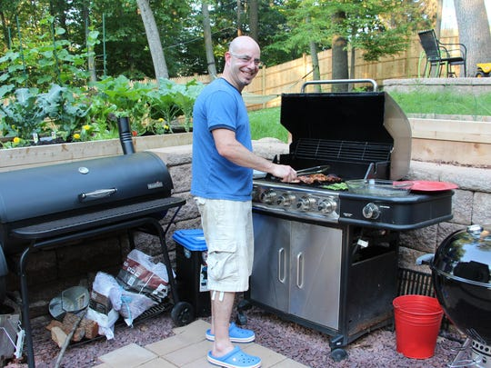 Josh Feldman of Morristown cooks a simple weeknight dinner on the grill, which includes marinated chicken breasts and seasoned asparagus, prepared by his wife, Rachel.