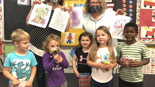 Children from Lilliput Learning Center with their teachers, Michelle Chiddister and Wendy Rodewald, with the Halloween pictures they shared with Thurston Woods residents and the treats they received in return.