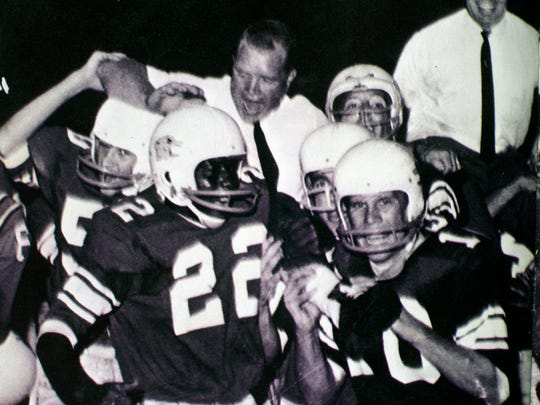 Head coach Tom Bass, left, and assistant coach Jack Ogle are carried from the field after Sevier County High School upset Young High School 13-0 on Aug. 30, 1963. Running back Charles Moulden is number 22. (Sevier County High School Yearbook)