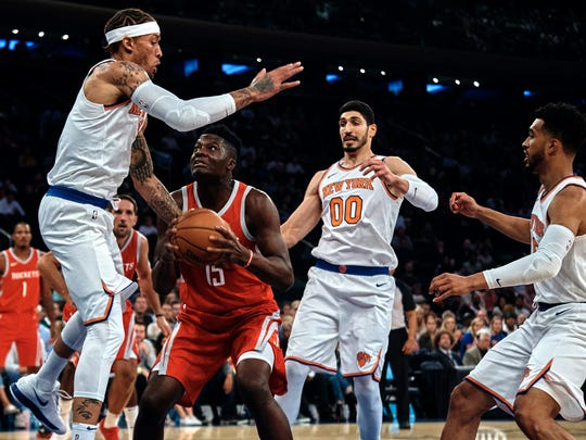 Houston Rockets' Clint Capela drives to the basket against New York Knicks' Michael Beasley, left, and New York Knicks' Enes Kanter, during the first half of a preseason NBA basketball game at Madison Square Garden in New York, Monday, Oct. 9, 2017.