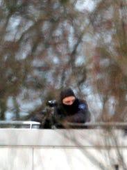 A hooded police officer stands on a roof in Dammartin-en-Goele,