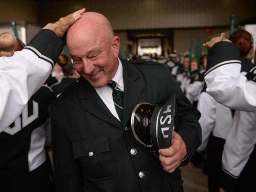 Members of the Spartan Marching Band rub the head of