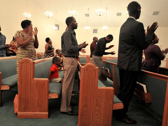 African congregants sing and clap hands during services